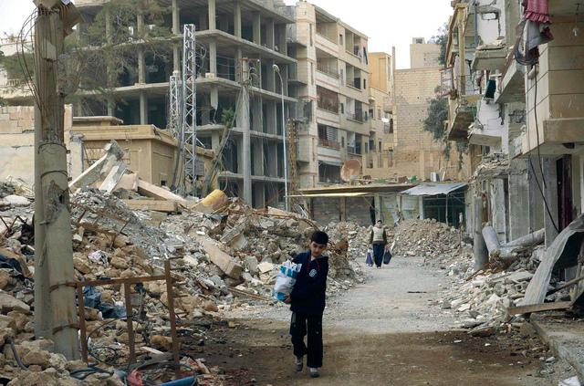 Boys carrying bags walk through damaged areas in Deir al-Zor