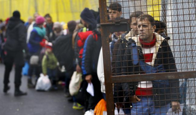 Migrants wait to cross the border from Slovenia into Spielfeld in Austria
