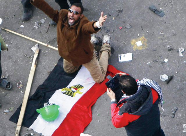 A protester, kneeling on the Egyptian flag, shouts slogans during clashes at Tahrir Square in Cairo